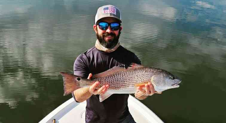 a fisherman with a redfish